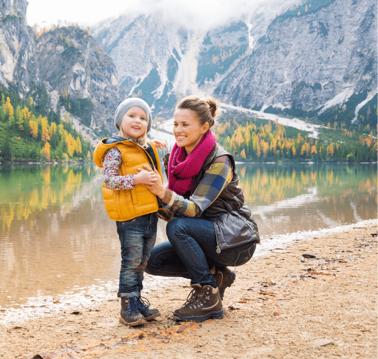 Caucasian mother with her young daughter in front of a lake and mountains.