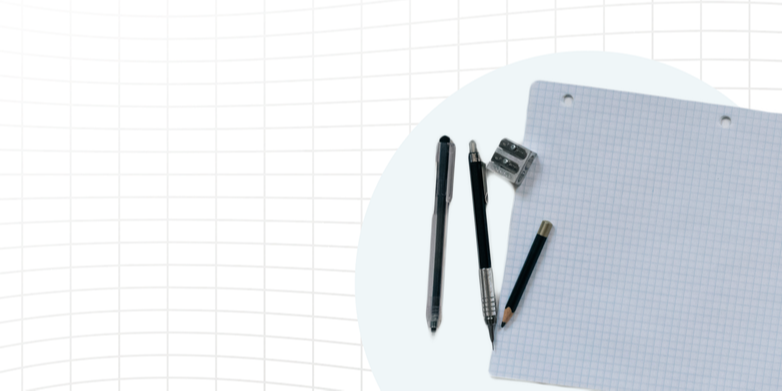 Pens, a pencil, and a small sharpener on top of grid paper.