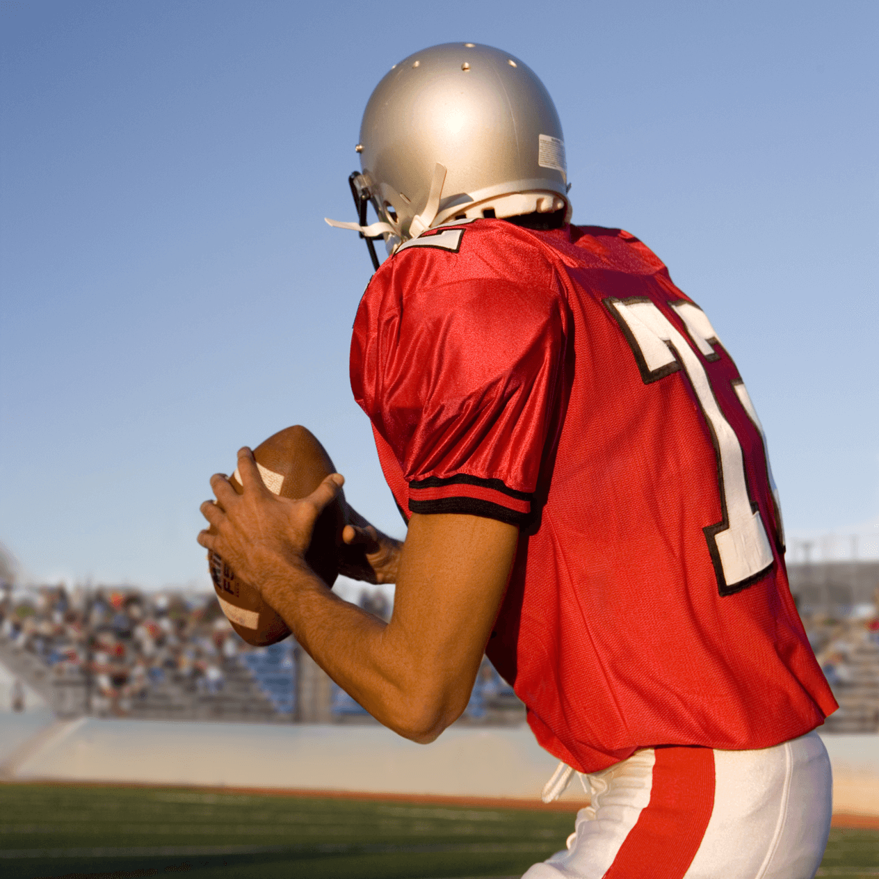 American football quarterback wearing a red jersey perparing to throw the ball.