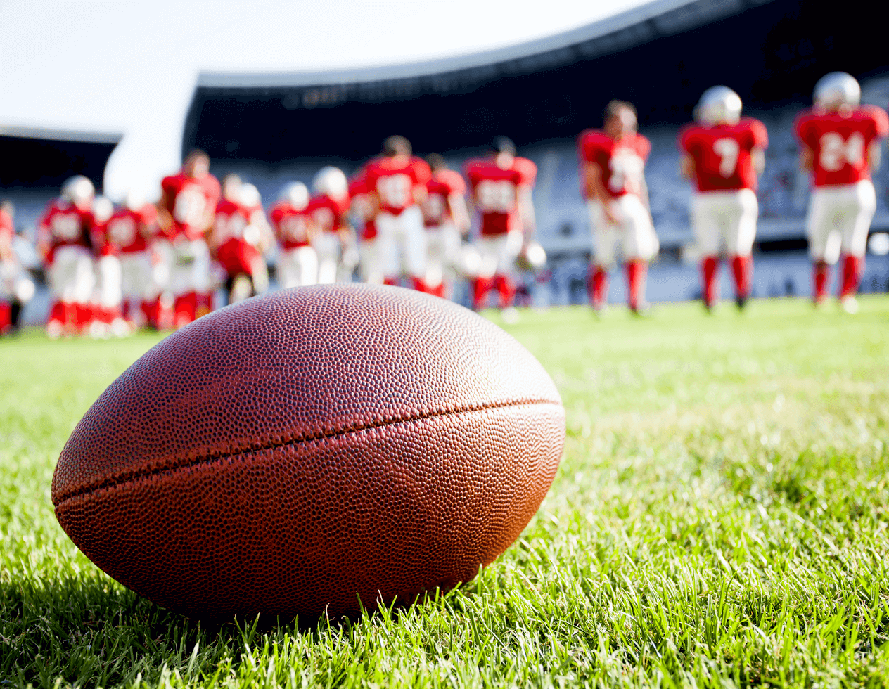 Photo of a football on a field with a team of players wearing red jerseys standing behind it in the background.