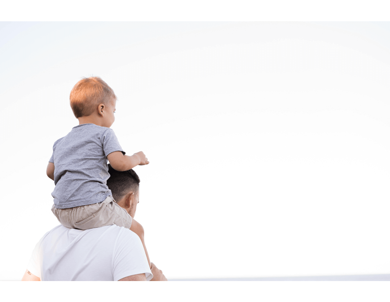Man with son on his shoulders on a white background.