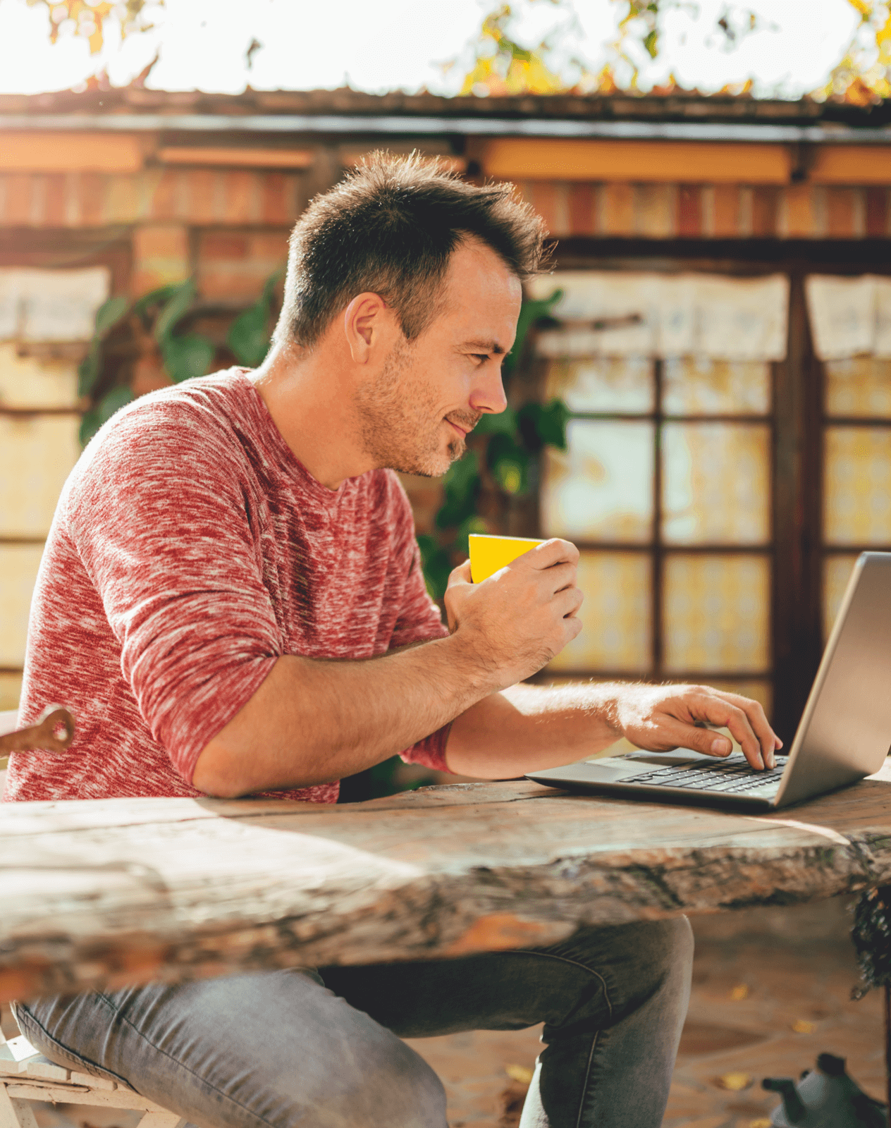Caucasian man in a pink shirt working on a laptop computer while drinking a cup of coffee in his backyard.