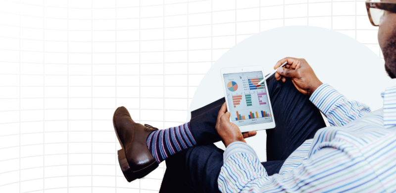 Crossed legs of a man wearing striped socks and holding a tablet with graphs/dashboard on it.