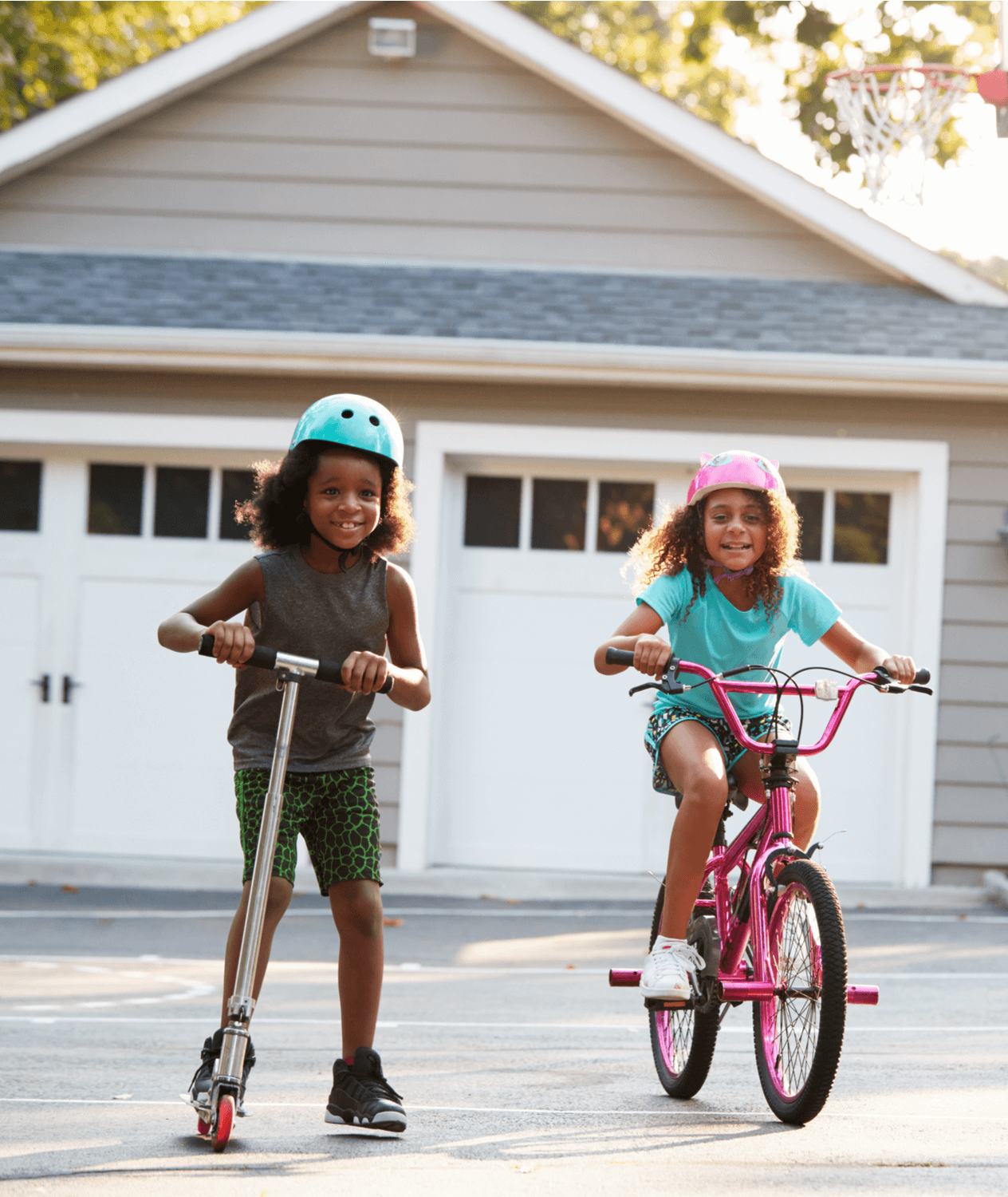 Portrait of two young African American girls. One is riding a scooter and the other is riding a bike.